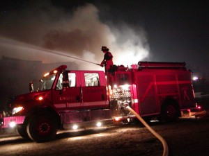 A firefighter stands on top of a fire truck and uses to hose to fight a fire as smoke rises behind h