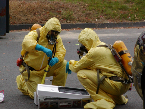 2 people in yellow hazmat suits and oxygen masks work with a fire fighting device