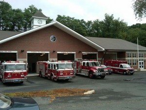 Fire trucks sit in the parking lot of the fire station and garage