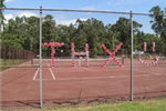 Solo cups stick into the open spaces of a rusty mesh fence that encloses a clay tennis court